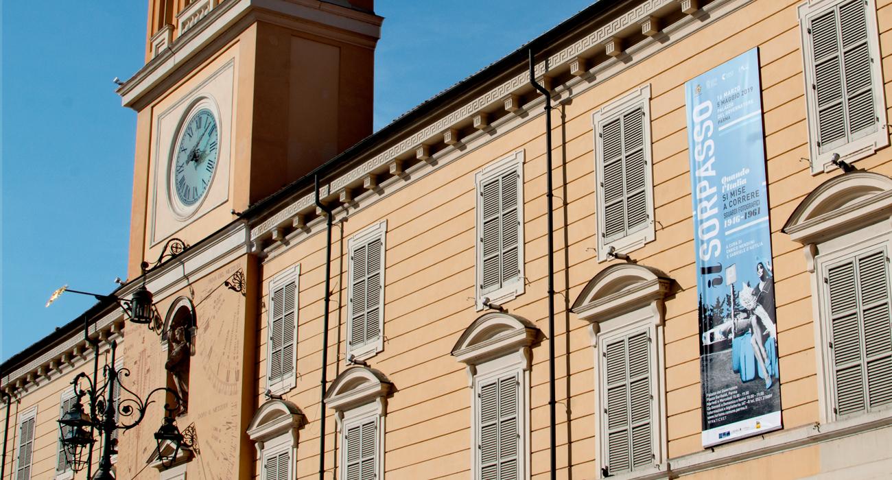 Lo stendardo della mostra il Sorpasso sulla facciata del Palazzo del Governatore a Parma